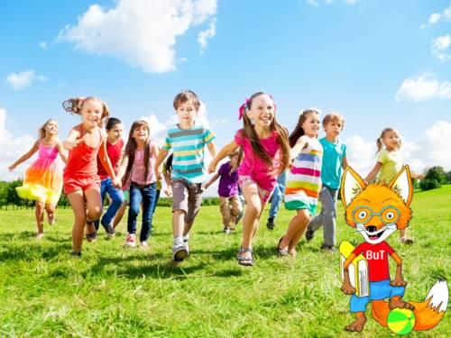 Laufende Kinder auf einer grünen Wiese. Die Kinder halten sich anden Händen.