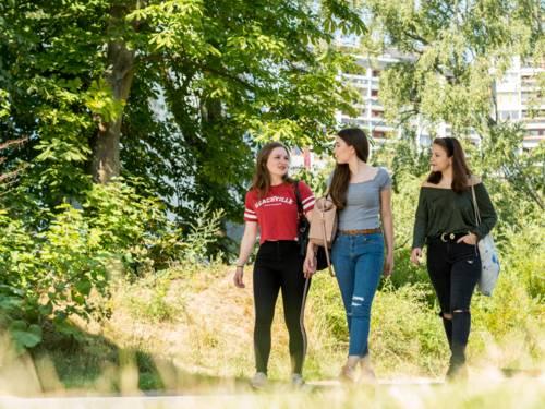 Dre Mädchen gehen durch eine Grünfläche, im Hintergrund sind Wohnhäuser für mehrere Parteien.