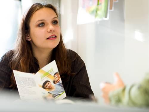Ein Mädchen sitzt an einem Tisch und hält einen Flyer der Jugendberufsagentur in ihrer Hand.