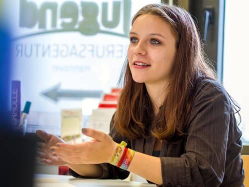 Eine Frau sitzt an einem Tisch, gestikuliert mit den Händen und schaut zu einem Gegenüber, welches sich aber nicht im Bildausschnitt befindet.