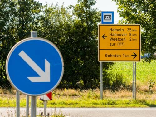 Im Vordergrund das runde Verkehrszeichen für vorgeschriebene Vorbeifahrt (rechts vorbei) mit einem weißen Pfeil auf blauem Grund, der nach rechts unten zeigt und im Hintergrund ein Wegweiser, der die Entfernung zu den Orten Hameln, Hannover, Weetzen und Gehrden zeigt.