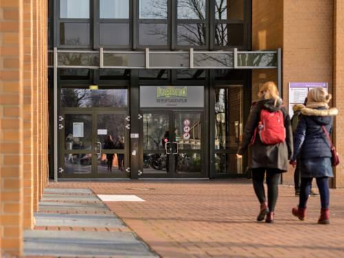 Zwei Jugendliche gehen auf die Tür der Jugendberufsagentur Hannover zu.