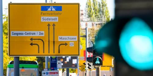 Ampeln für Autoverkehr, Fußgänger und Radfahrende stehen auf Grün, ein Wegweiser weist dem Verkehr den Weg in verschiedene Richtungen.