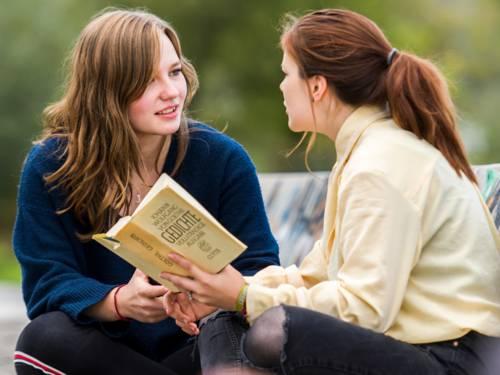 Zwei Jugendliche sitzen auf der Bank, eine der beiden hält einen Gedichte-Band in ihren Händen.