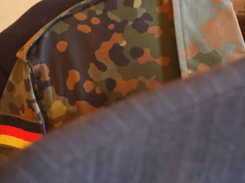 Auf einer Kleiderstange hängt ein Nadelstreifenanzug, dahinter ist eine Bundeswehr-Feldbluse in Tarnmuster.