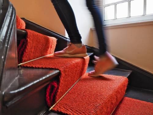 Jemand geht eine Treppe hinauf, auf den Stufen liegt roter Teppich.