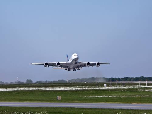 Ein großes Passagierflugzeug startet von einem Flughafen. Das Fahrwerk ist noch ausgefahren, es hebt gerade ab.
