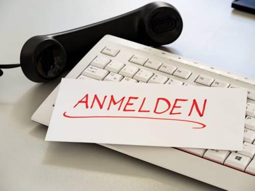 """Schriftzug """"Anmeldung"""" auf einer Tastatur, daneben liegt ein Telefonhörer"""