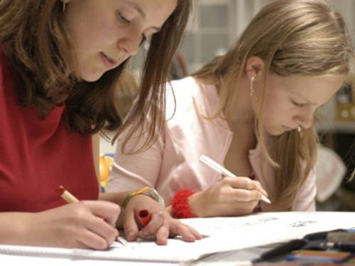 Zwei Schülerinnen an einem Tisch, die konzentriert an Aufgaben auf Arbeitsblättern arbeiten.