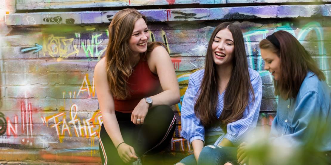 Drei Mädchen sitzen vor einer bunt besprühten Hauswand.
