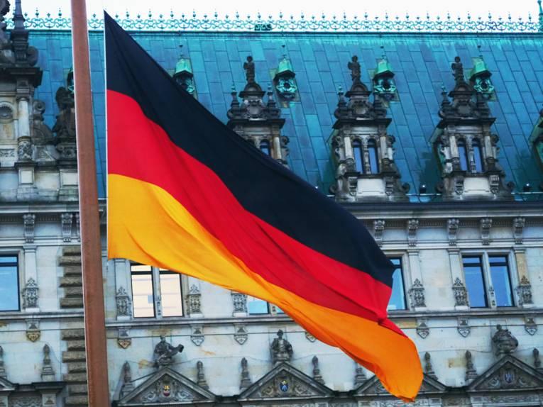 Eine Flagge in den Farben Schwarz, Rot und Gold weht im Wind vor einem historischen Gebäude.