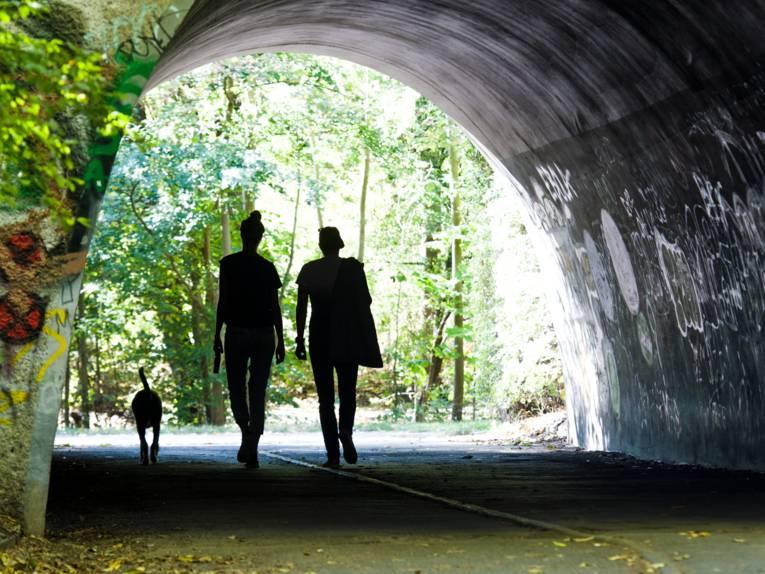 Zwei Menschen und ein Hund gehen durch einen Tunnel.