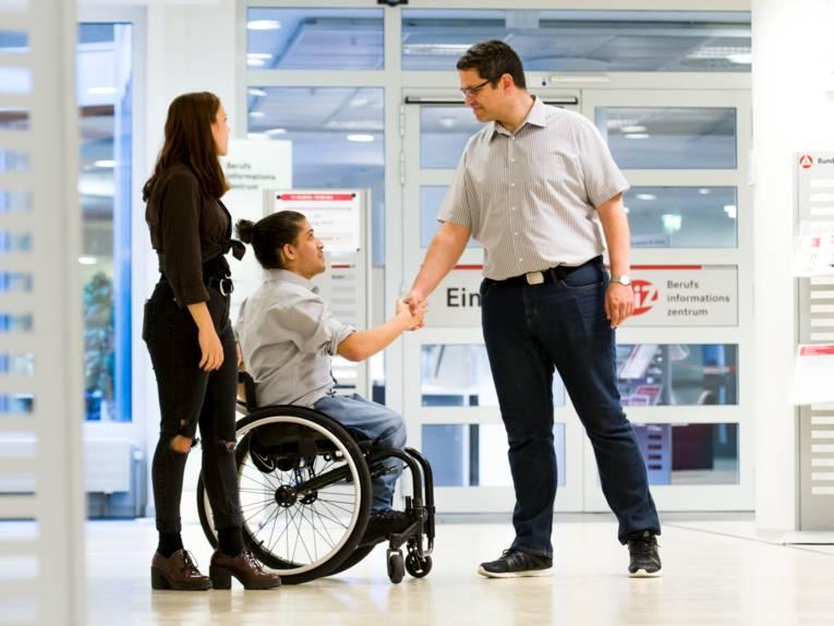 Ein Jugendlicher und ein Mann schütteln sich die Hände, eine Jugendliche steht daneben. Im Hintergrund ist die Tür zum BiZ (Berufsinformationszentrum) zu sehen.