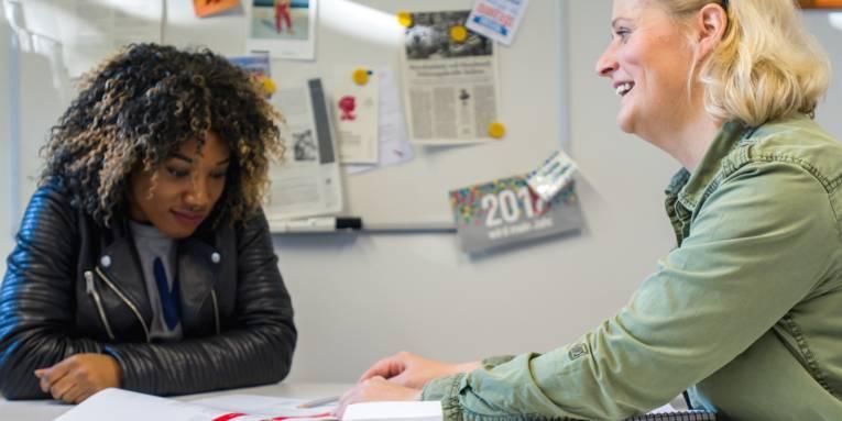 Eine Jugendliche schaut auf den Stift, mit dem eine Frau etwas in einer Broschüre zeigt.