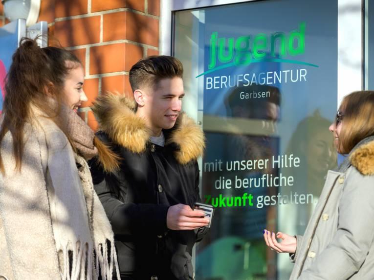 Drei Jugendliche stehen vor dem Eingang der Jugendberufsagentur (JBA) Garbsen.