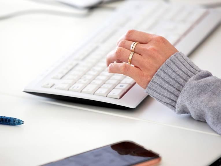 Eine Hand ist über einer Computertastatur, ein Smartphone liegt daneben.