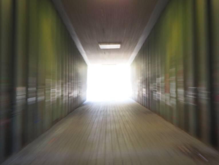 Effekt fliehender Linien zur Mitte durch Reißzoom: Am Ende eines Tunnels strahlt helles Licht.